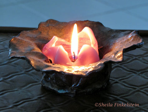 lit candle with triangular shapes