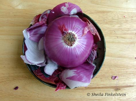 Partially peeled red onion in a ceramic dish with the outer skin and firt layer